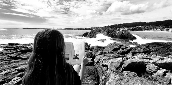 Joven leyendo sentada en unas rocas frente al mar.